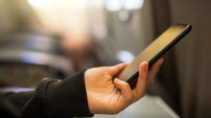 Woman using smartphone in airplane during flight