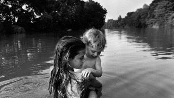 CANADA. Lambton County, Ontario. Two-year-old Isaac TOWELL is carried into the Sydenham River by his older sister Naomi to introduce him to water. 1996. Only for use in direct connection with publicity for the Magnum Photos Square Print Sale, 'Closer' from 5 - 10 June 2017. Any unauthorised image use will be charged for by Magnum Photos.