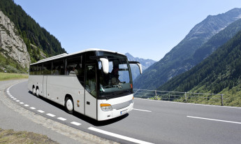 Blue sky over white bus crossing the alpes